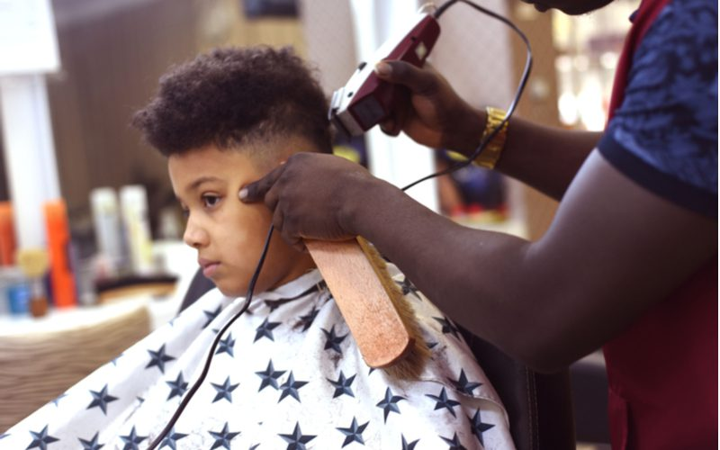 Kid getting an afro buzz from a barber holding a long brush to his chin