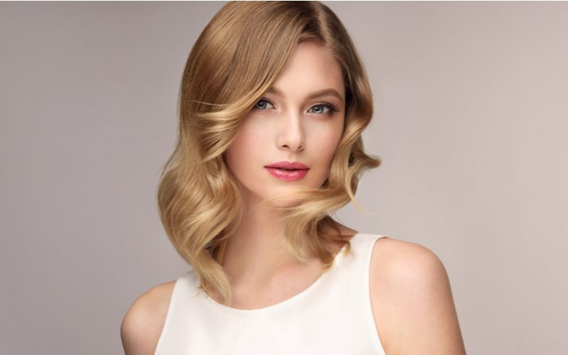 Woman with a choppy long bob haircut with curls stands seductively in a studio