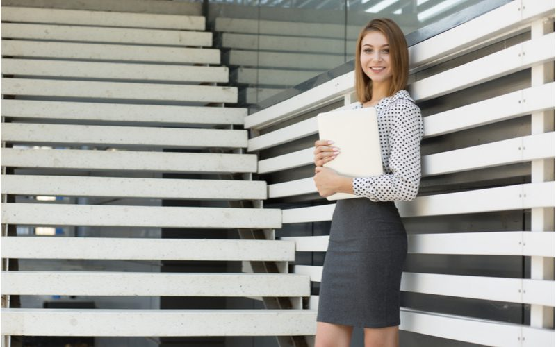 Slightly angled choppy long bob on a woman holding a binder in a tight skirt