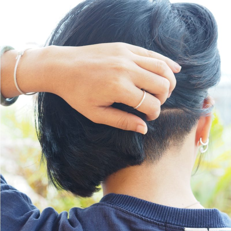Subtle Bob Undercut on an Asian woman standing outside in front of greenery