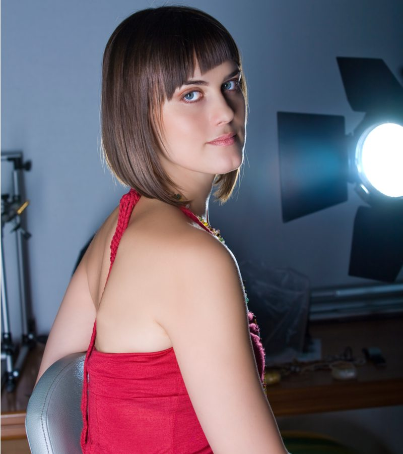 A-Line Inverted Lob With Asymmetrical Bangs on a woman in a red dress in front of a studio light