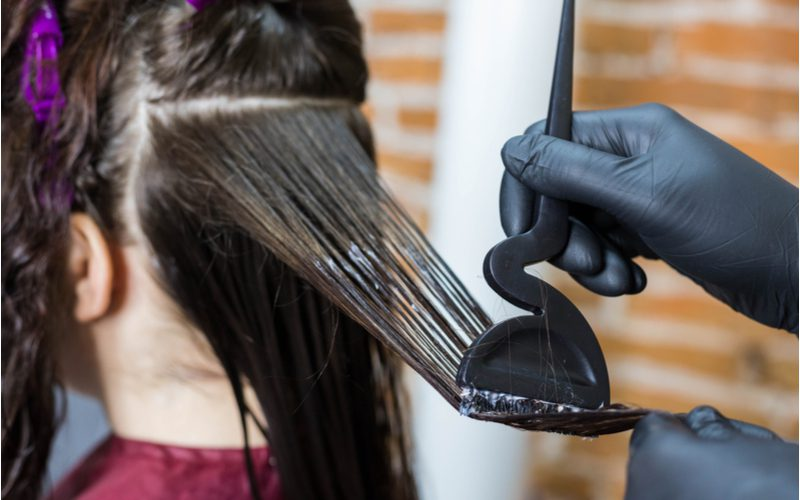 Woman getting rid of a perm with a keratin treatment from a hair stylist in black rubber gloves in a salon