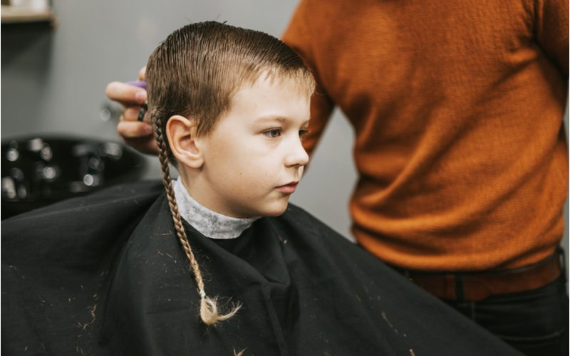 Boy with braids for men sitting in a barber's chair next to a guy in an orange sweater