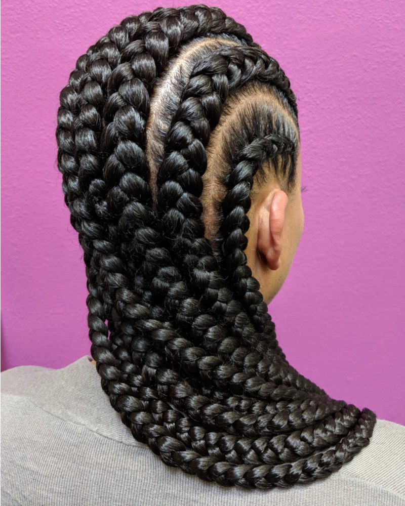 Black woman wearing a jumbo braid hairstyle standing in front of a purple wall