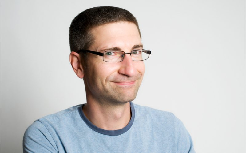 Man in glasses has a straight line buzzcut in a blue ringer shirt