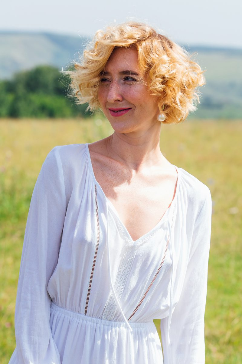 Chin-Length and Curly Stacked Bob Worn by a Woman in a Field