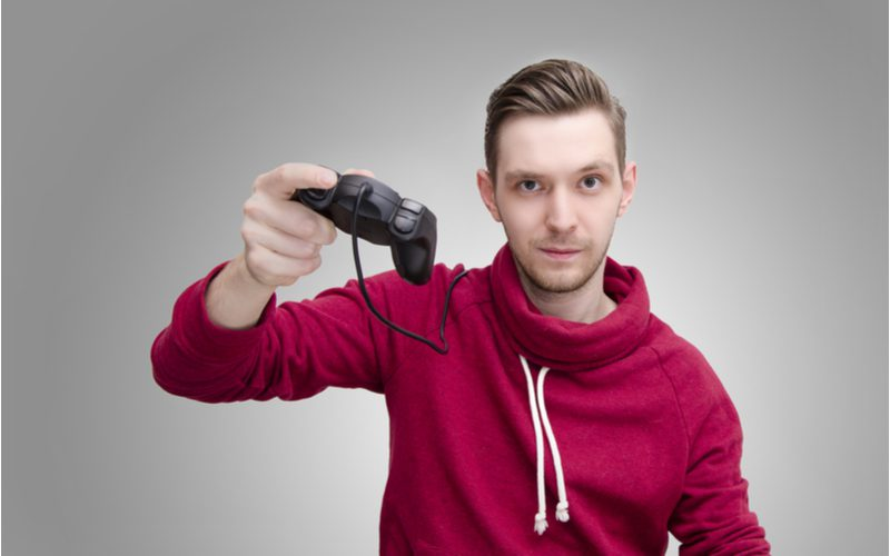 Image to show how to slick back hair with a guy in a red hoodie holding a gamecube controller