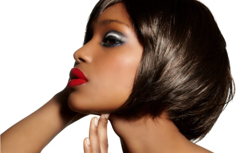 Relaxed and layered bob haircut on a black woman with red lips standing in a white room