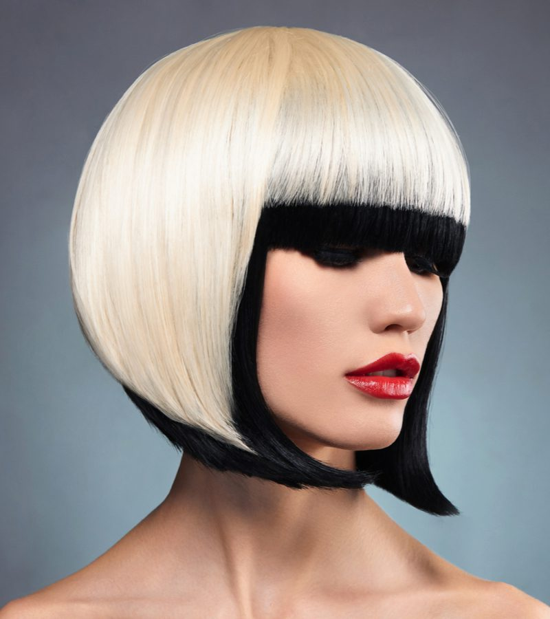 Color contrast on a woman with blonde hair with black ends wearing red lip with a face-framing inverted bob