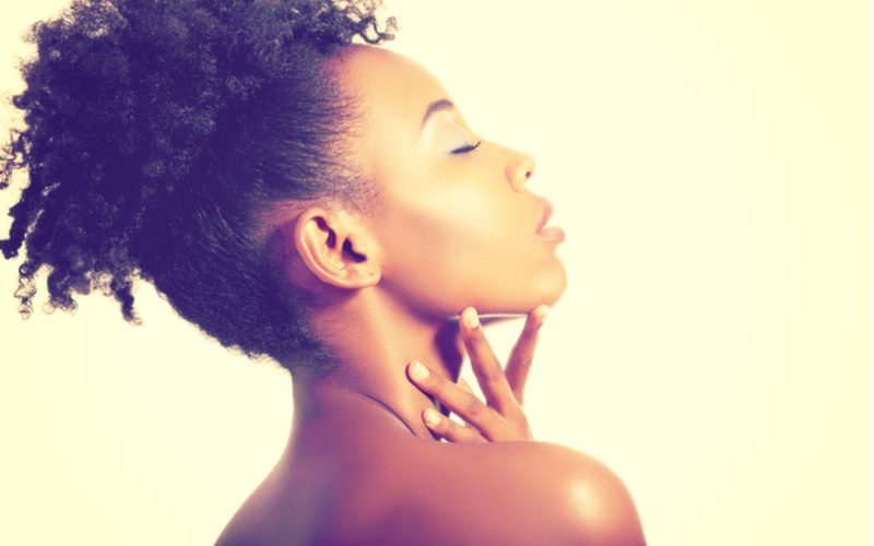 High puff ponytail hairstyle on a black woman closing her eyes and looking up