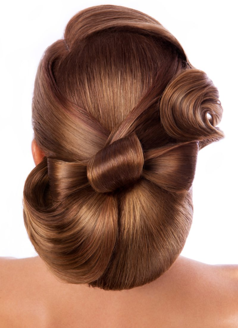 For a featured mother of the groom hairstyle, a woman tied her hair into a bow and posed in a studio for this image