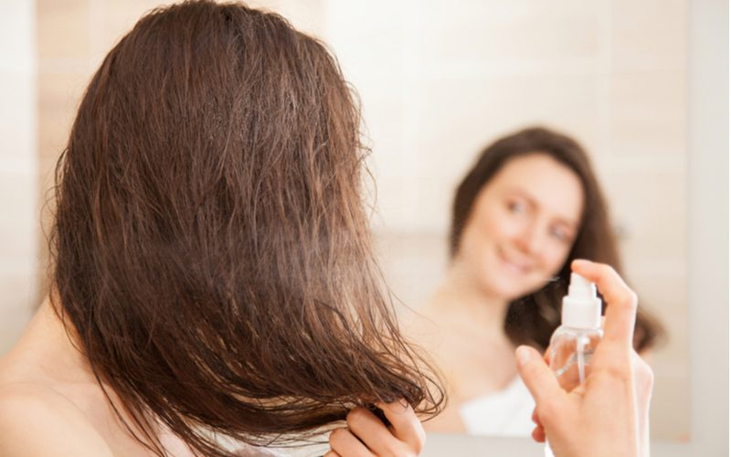 Smiling woman applying pre-treatment spray to her hair before diffusing