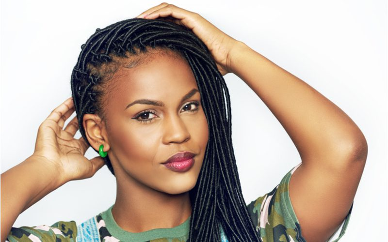 For a piece on tribal braids, a woman with Micro Faux Locs holds her head