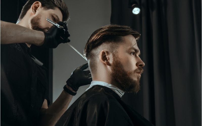 Low fade haircut on a guy with long slicked-back hair on top and a beard