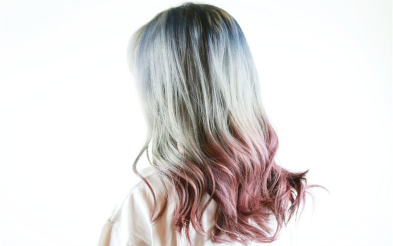 Lady in a white shirt with ombre hair with feathered tips faces away from the camera