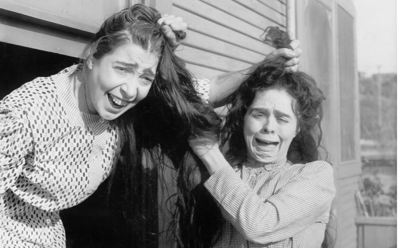 Black and white photo of two women pulling each other's hair for a piece on what is hair cracking