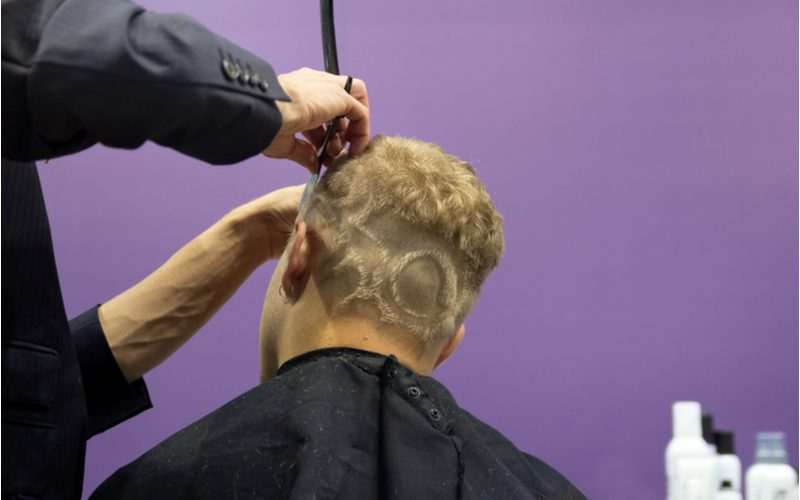 Man with a unique hairstyle pattern gets the top of his head trimmed up